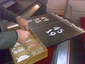 Klokker Jens Ågedal henger opp salmenummer på tavlene i 2008